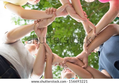 Close-up of hands of young adults joined in a circle on the foreground - stock photo