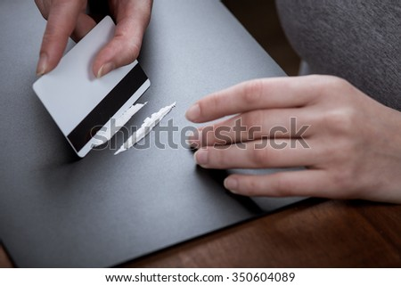 Close up of hands of young druggie is doing tracks of cocaine with a credit card - stock photo