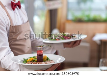 Close up of hands of young waiter holding two plates of delicious food - stock photo