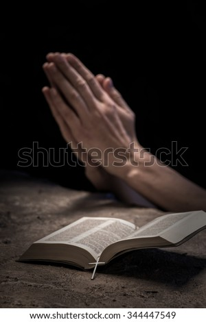 Close up of hands of young woman praying near the Bible. She is clapping her arms together