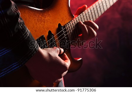 close up of hands playing an electric guitar