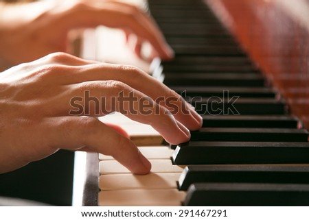 Close-up of hands playing the piano - stock photo
