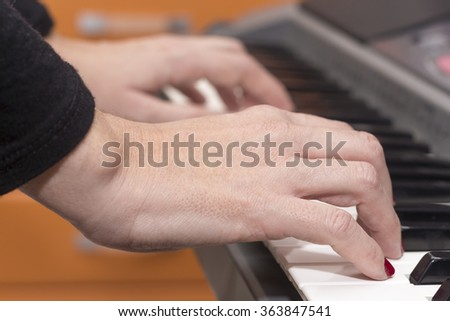 Close-up of hands playing the piano at home - stock photo