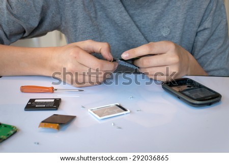 Close up of hands repairing  or disassembling a mobile phone - stock photo