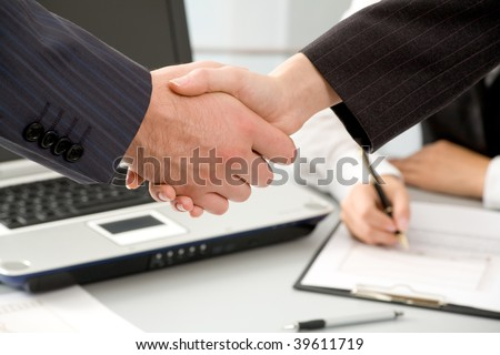 Close-up of hands shake between two successful business people: man and woman