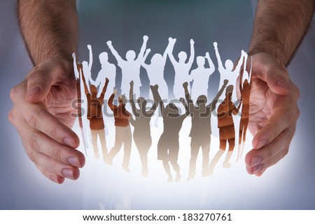 Close-up Of Hands Taking Care Of Paper Cut Out Of Human Figure - stock photo