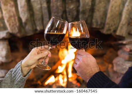 Close-up of hands toasting wineglasses in front of lit fireplace - stock photo