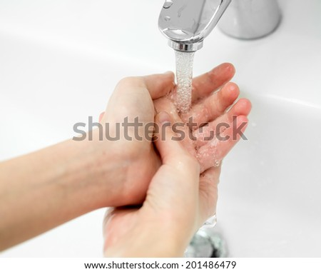 Close-up of hands under stream of water from faucet - stock photo