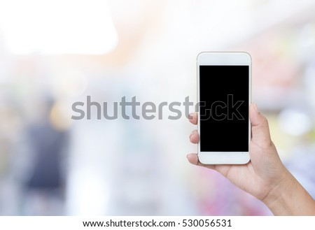 Close up of hands using smartphone on blurred background