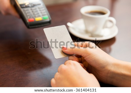 close up of hands with credit card reader at cafe - stock photo
