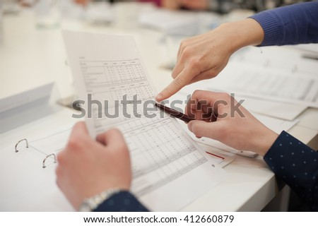 Close-up of hands with pen over paper during conference - stock photo