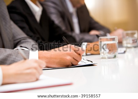 Close-up of hands with pens making notes during conference - stock photo