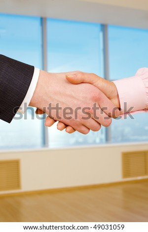 Close-up of handshake of two businesspeople after signing promising contract - stock photo