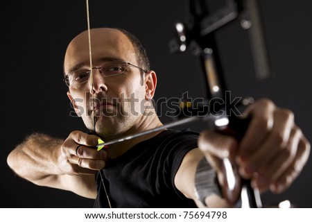 Close up of handsome archer in black on black background aiming with bow and arrow, side view with focus on eyes. - stock photo
