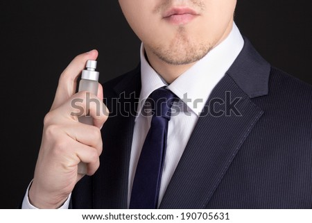 close up of handsome young business man using perfume - stock photo