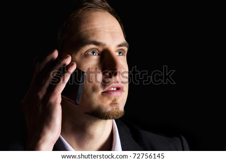 Close up of handsome young businessman in dark suit  talking on mobile-phone and looking up, low-key image isolated on black background. - stock photo