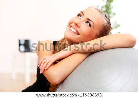 Close up of happy and beautiful woman with fitness ball at home