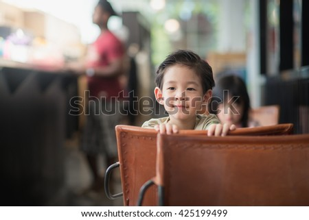 Close up of happy Asian child in a vintage cafe - stock photo