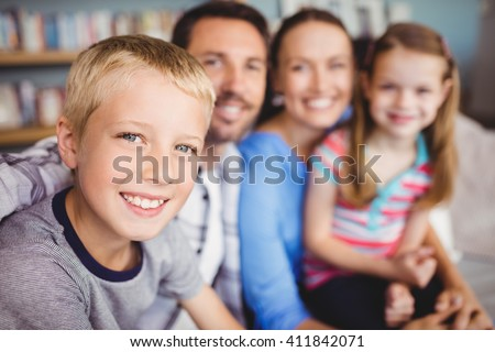 Close-up of happy boy with family on sofa at home - stock photo