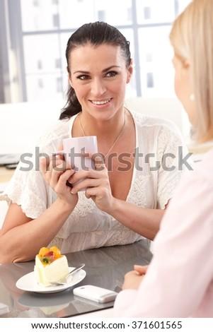 Close up of happy casual brunette businesswoman with coffee cup and cake at business office, smiling. - stock photo