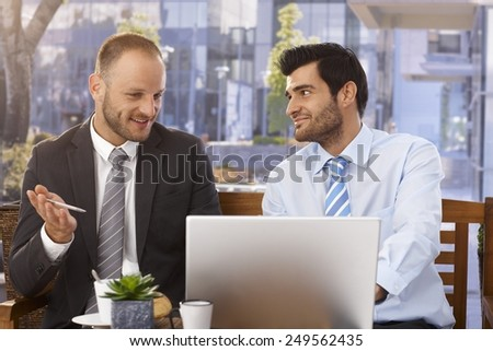 Close up of happy caucasian businessmen discussing ideas on laptop computer, outdoors. - stock photo
