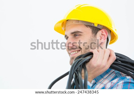 Close-up of happy electrician with wires over white background