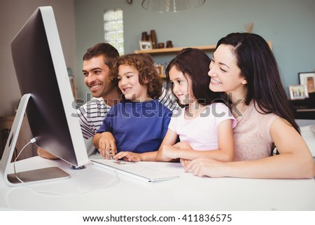 Close-up of happy family looking in computer at home - stock photo