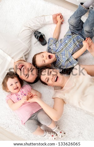 Close-up of happy family  lying on carpet and looking up - stock photo