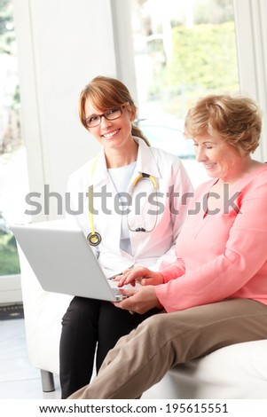Close-up of happy female doctor consulting  with senior patient at small clinic. - stock photo