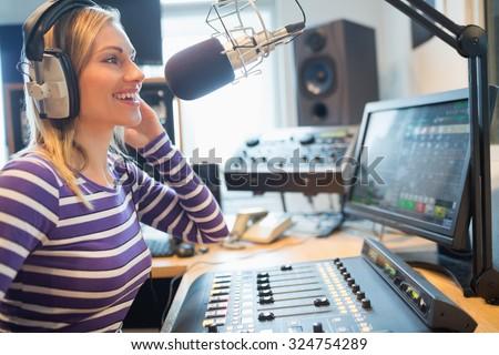 Close-up of happy female radio host broadcasting through microphone in studio - stock photo