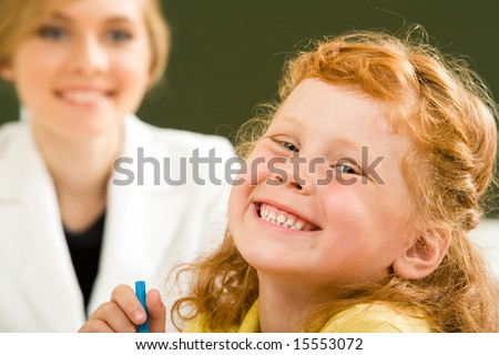 Close-up of happy girl laughing while looking at camera on background of smart teacher - stock photo