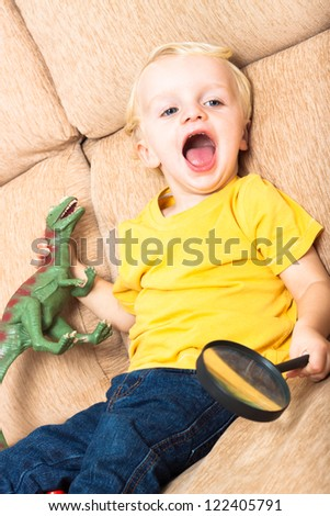 Close up of happy laughing child boy playing on sofa. - stock photo