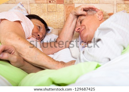 Close up of happy loving senior couple relaxing in bed. - stock photo