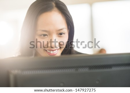 Close-up of happy mid adult businesswoman looking at computer in office - stock photo