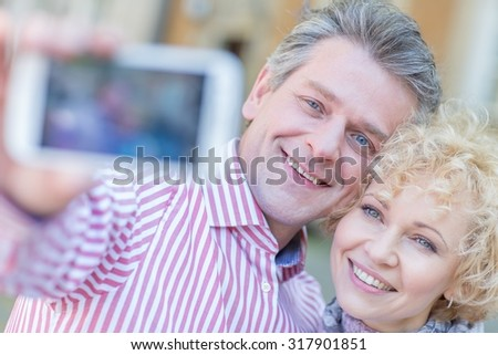 Close-up of happy middle-aged couple taking selfie through smart phone - stock photo