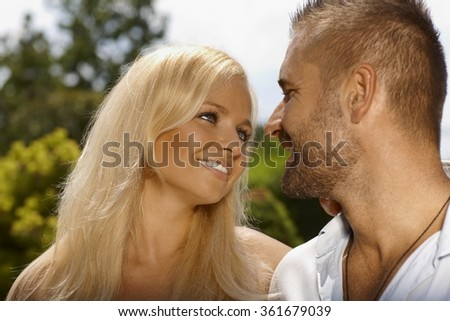 Close up of happy romantic young couple outdoor. Attractive blonde, smiling woman and stubbly handsome man. - stock photo