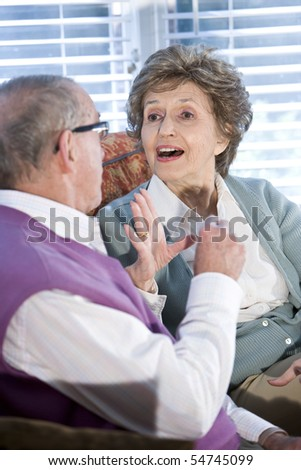 Close up of happy senior couple chatting together on couch - stock photo