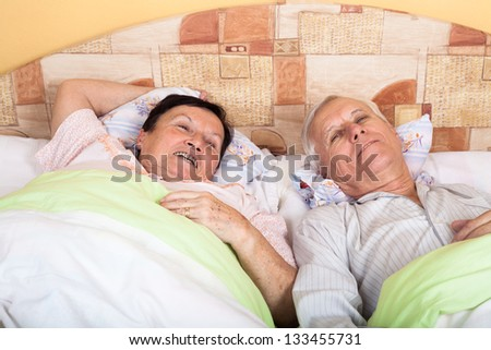 Close up of happy senior couple resting in bed. - stock photo