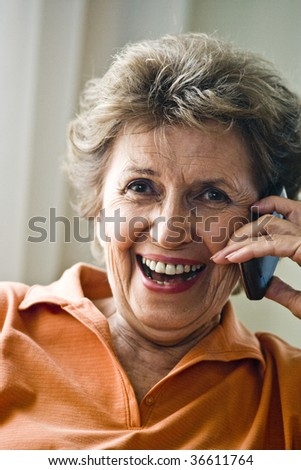 Close up of happy senior woman on mobile phone - stock photo