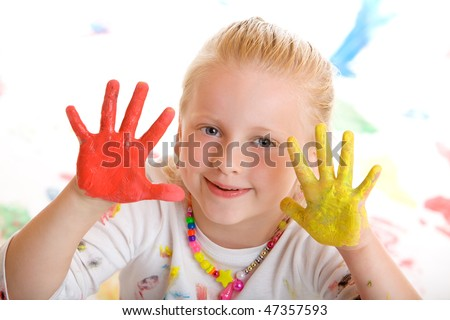 Close-up of happy smiling girl, playing with finger painting colour. - stock photo