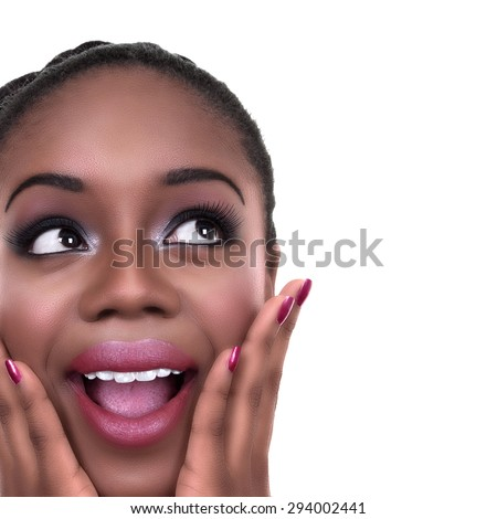 Close up of happy surprised excited black African American woman in make up and nail polish looking sideways at copy space - stock photo
