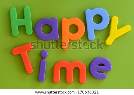 Close up of Happy Time words in colorful plastic letters on green background
