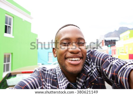 Close up of happy young man on the city street taking a self portrait - stock photo