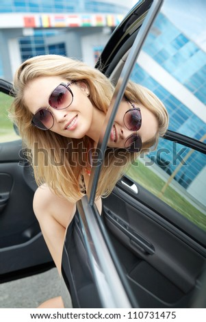 Close-up of happy young pretty woman looking at camera and sitting her car - stock photo