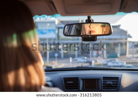 Close up of head of cheerful girl sitting at the steering wheel of her car. She is applying the lipstick on her lips. The lady is looking at the mirror with concentration. Copy space in right side - stock photo