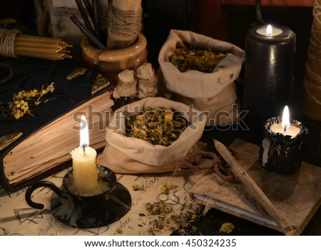 Close up of healing herbs, alchemist papers, books and black candles. Old pharmacy, esoteric or alternative medicine concept. Black magic and occult objects, medieval homeopathic ritual