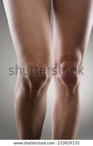 Close-up of healthy female legs over grey background. Knee joint care concept. - stock photo