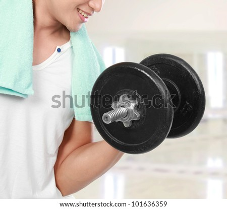 close up of healthy fitness man exercising with dumbbells in the gym