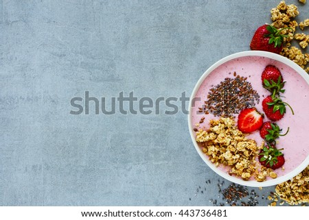 Close up of healthy strawberry smoothie bowl with fruits, cereals, seeds and nuts over light grey background, copy space, top view. Healthy food for breakfast and snack - stock photo