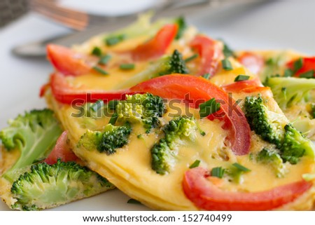 Close up of healthy tomato and broccoli omlette garnished with chives.